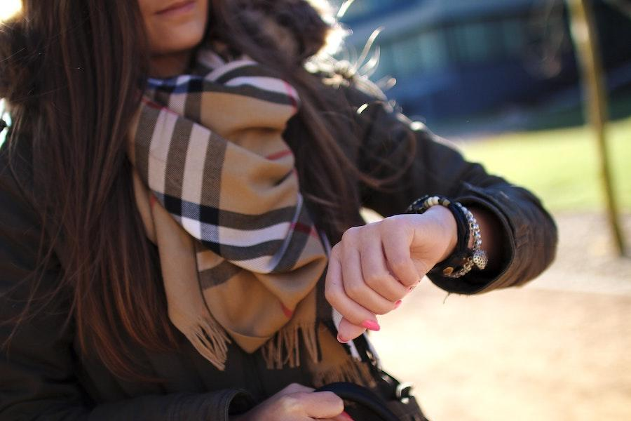 An image of a woman with a brown scarf and jacket as she looks down at her watch, which is on her arm along with a silver bracelet.