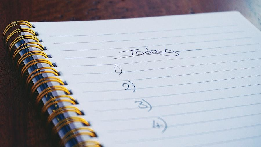 """An image of a notebook on a brown flat surface with the word """"Today"""" and the numbers 1 through 4 listed as a to-do list."""