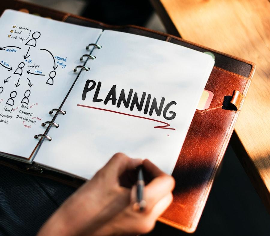 An image of a woman's hand holding a pen over a notebook that has a diagram on the left side and the word planning on the right side with a red underline.