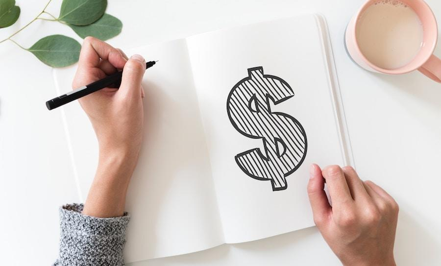 A woman's hands with a pen in her left hand after she drew a dollar sign on a white notebook.