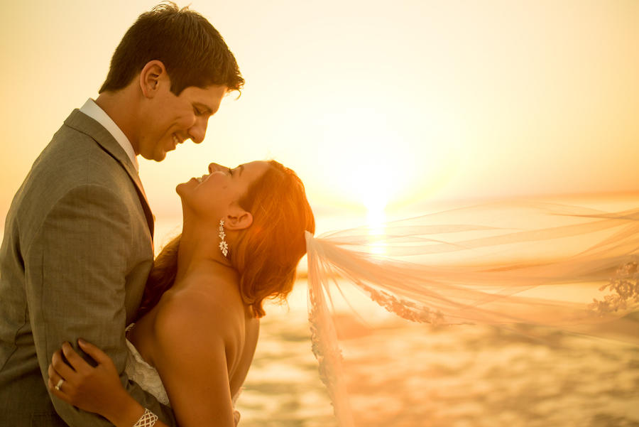 An outdoor golden hour wedding photo of the bride and groom in an embrace, with the bride's veil flowing in the wind.