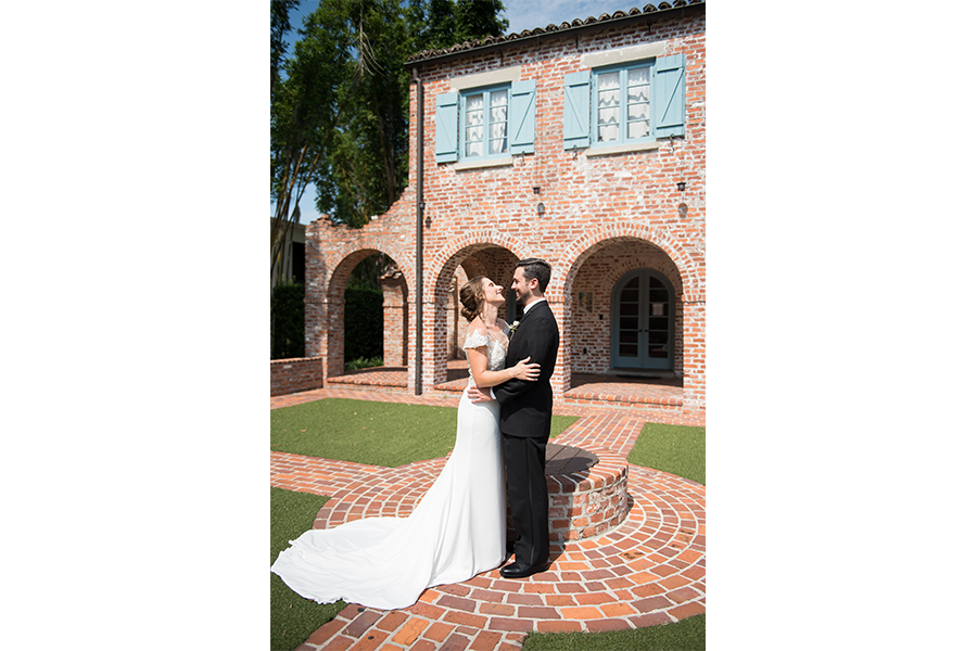 A wedding picture of the bride and groom outdoors in front of a building in an embrace, with their sides facing the camera.