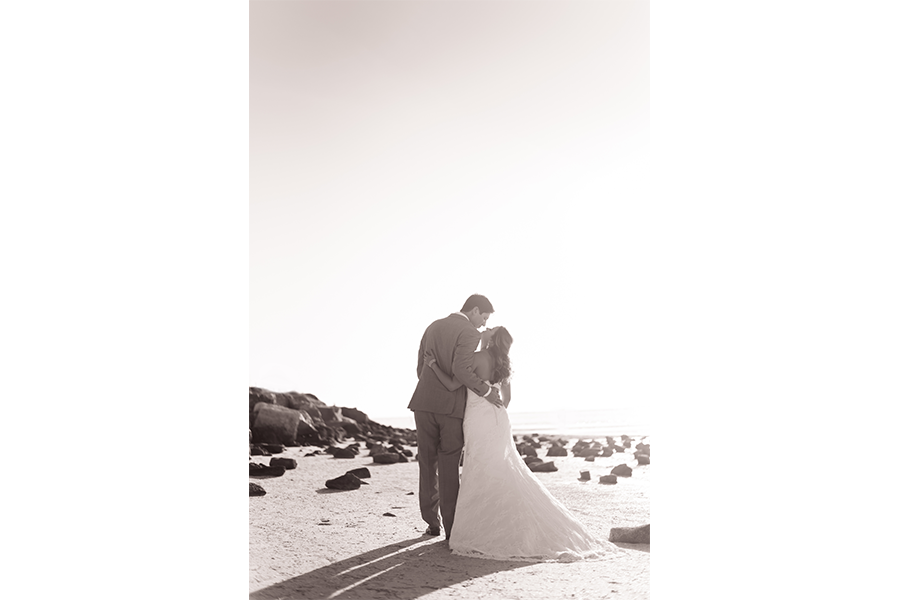 A film-like wedding image of the couple standing with their backs to the camera on a beach filled with rocks.