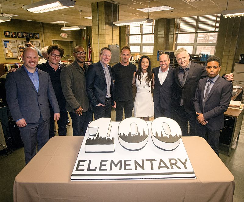 The cast of ELEMENTARY celebrates their milestone 100th episode with a cake-cutting ceremony Pictured (L-R) Bridget Wiley Executive Vice President, Current Programs, CBS Entertainment and CBS Television Studios, Glenn Geller President, CBS Entertainment, Executive Producers John Polson, Carl Beverly, Rob Doherty, Jonny Lee Miller Lucy Liu, David Stapf President, and CBS Television Studios Aidan Quinn, Jon Michael Hill and Kim Metcalf Photo: JEFF NEIRA /CBS ©2016 CBS Broadcasting Inc. All Rights Reserved.