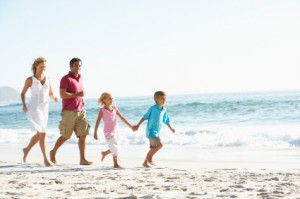 Young Family Running Along Sandy Beach On Holiday