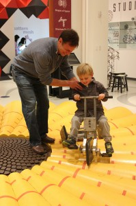 A visitor enjoys MoMath's square-wheeled tricycle.
