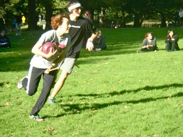 An NYU Quidditch player clutches a quaffle ball as she dashes down the field during game practice.