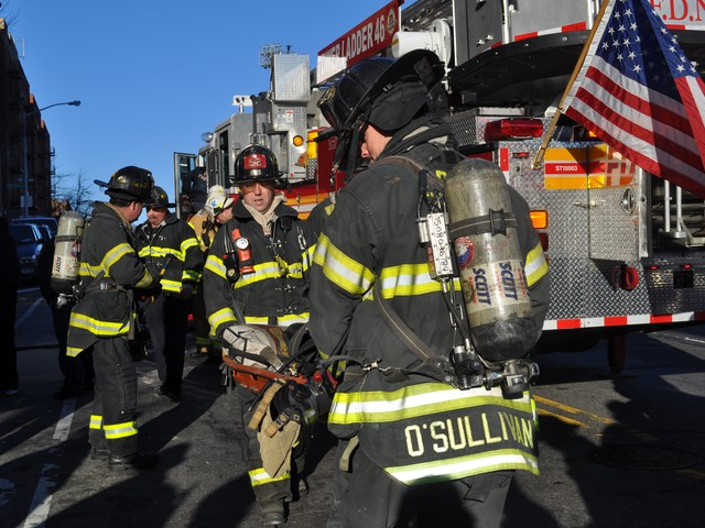 Firefighters carry equipment used to battle the blaze.
