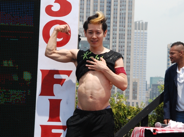 Hot dog eating champ Takeru Kobayashi poses for the camera after devouring 69 hot dogs at a contest in the Flatiron District, July 4, 2011.