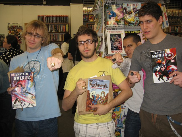 Three students from the School of Visual Arts celebrate their stash of free comics with their best Green Lantern poses.
