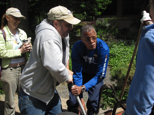 City Council Member Robert Jackson helps community volunteers pump a wheelbarrow's tire.