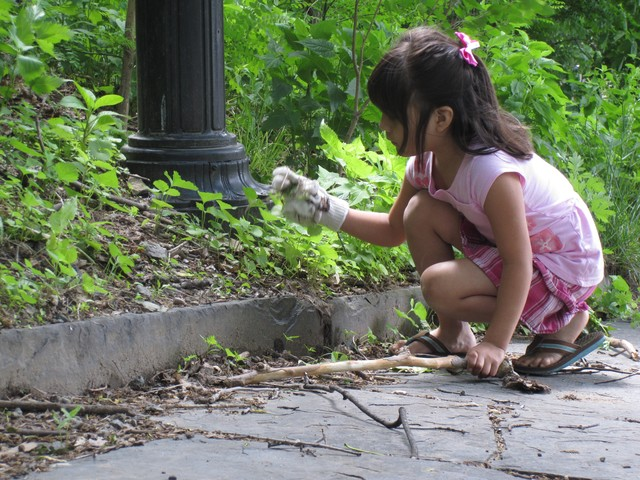 A girl examines the weeds she pulls out of ground before tossing them to the side.