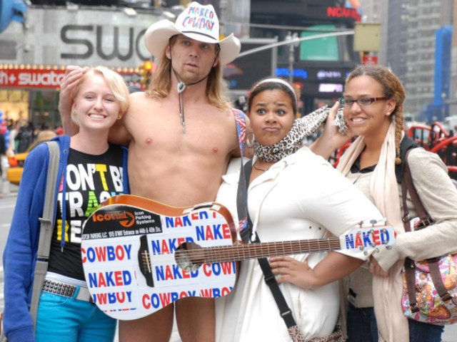 Naked Cowboy, Robert Burck, poses with fans.