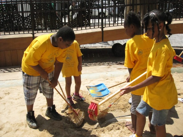 Local campers worked on a canal, using rakes to dig into the sand.