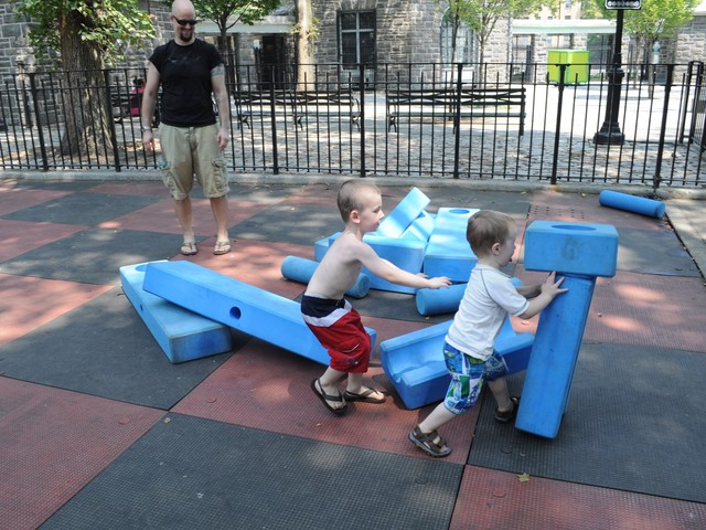 Owen and Liam Wells knock down blocks at the playground.