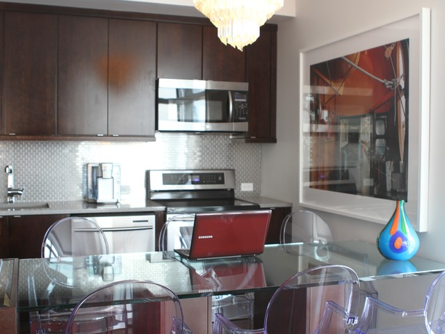 The ultramodern kitchen is by a living room furnished with antiques.
