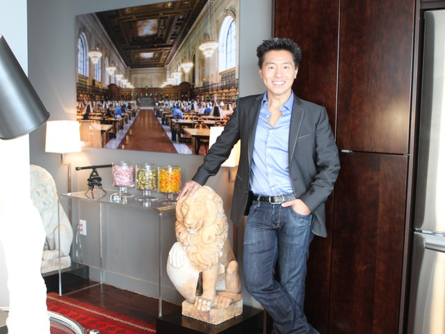 Interior designer Vern Yip leans against an antique marble lion in the foyer.