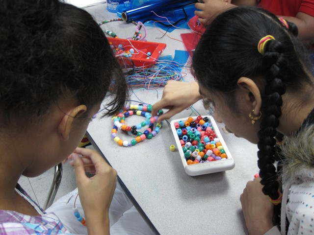 Valerie Liranzo, 14, and Kalsoom Ali, 14, make necklaces with beads at an art class for Jewish Guild for the Blind students.