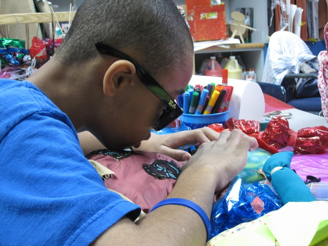 Visually impaired student Eli Jackson uses both his hands and eyes to look at a doll he made in art class.