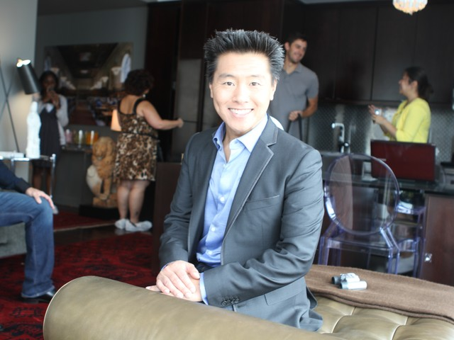 HGTV interior designer Vern Yip poses in the living room/dining room on a multifunctional couch.