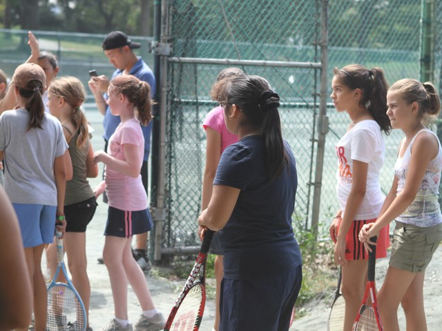 A group of girls look on to support their teammates during the tennis competition Tuesday.