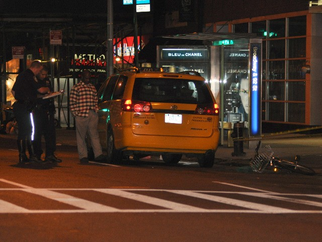 Police talk to the cab driver after the accident.