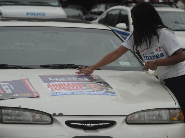 A woman tapes a poster to a car.