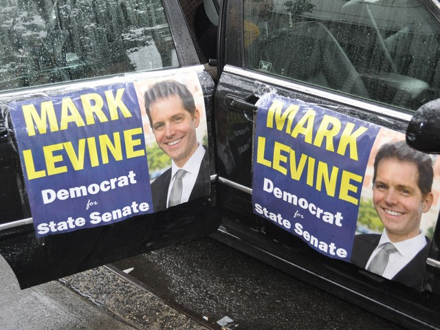 Car doors decorated with Levine posters.
