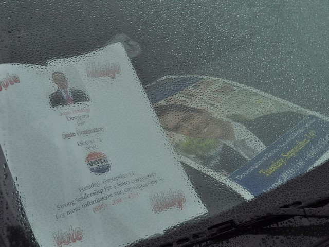 Posters inside one car at the Levine caravan are hidden by rain droplets on the windshield.