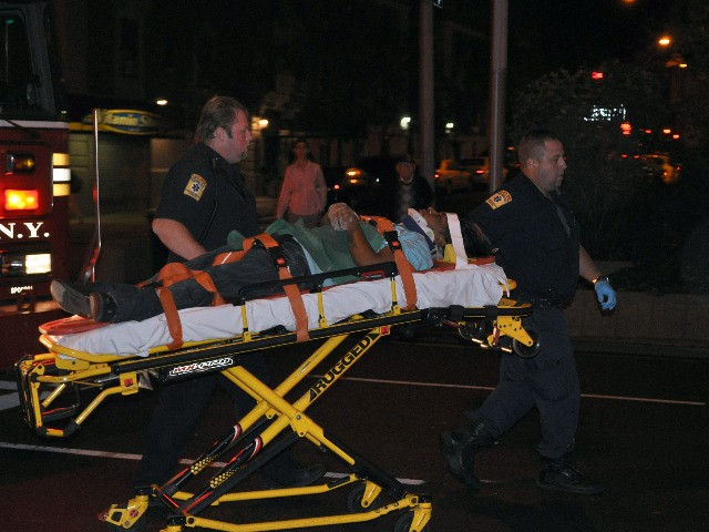 Emergency responders carry the deliveryman into an ambulance.