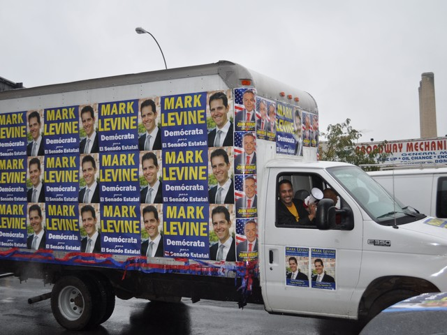 A cube truck papered with Levine posters leads the caravan down Broadway from 215th Street.