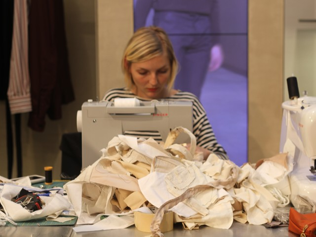 Parsons Design student Marie Claire Brush, 21, sews behind a giant pile of fabric.