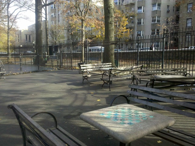 The chess tables are separated by a short fence from the playground area in Inwood Hill Park.