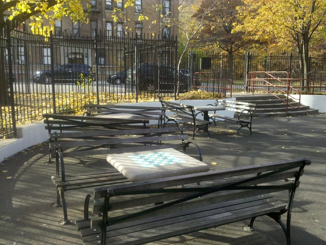 Stone tables with chess and backgammon boards line the edge of the Emerson Playground area in Inwood Hill Park, where locals are demanding access for all.