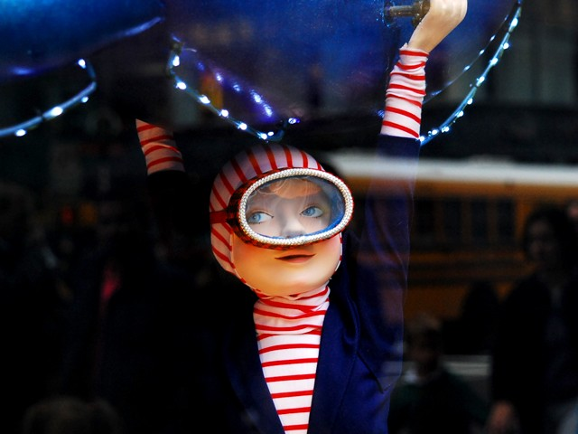 A little boy swings from a mechanical octopus in the window of Saks Fifth Avenue.