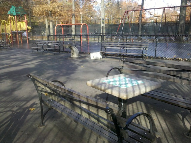 Chess tables at Inwood Hill Park overlook the playground.