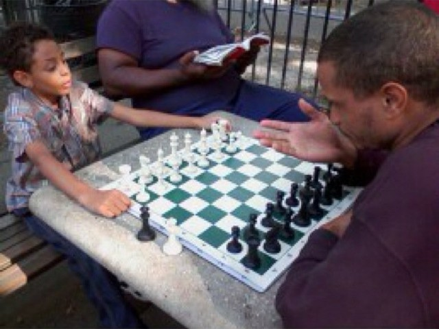 One of the seven men ticketed by the NYPD teaches chess to a new pupil in this photo.