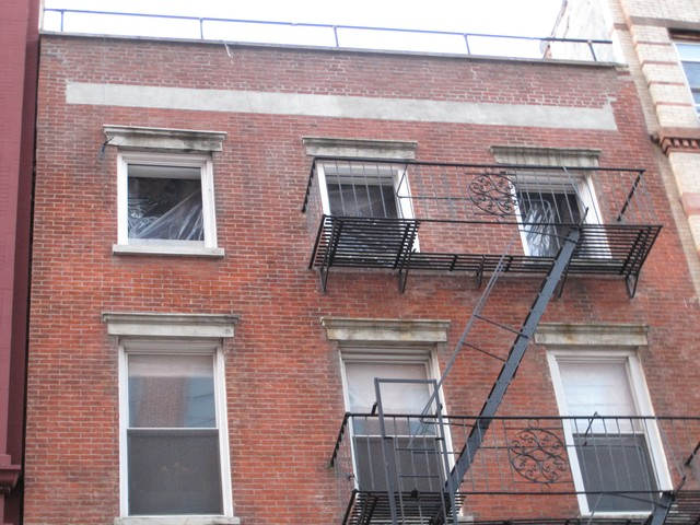 Three windows on the top floor of the five-story apartment building were blown out following the fire.