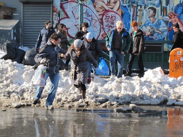 People crossed over a snow bank to avoid passing through the puddle.
