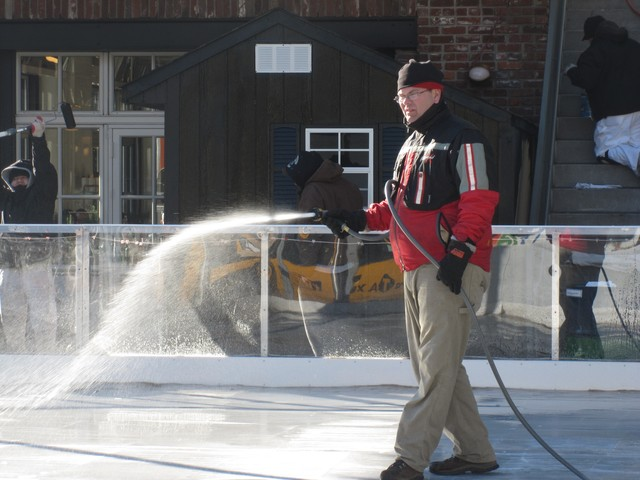 A worker sprays water for freezing on The Standard's ice rink Friday morning.