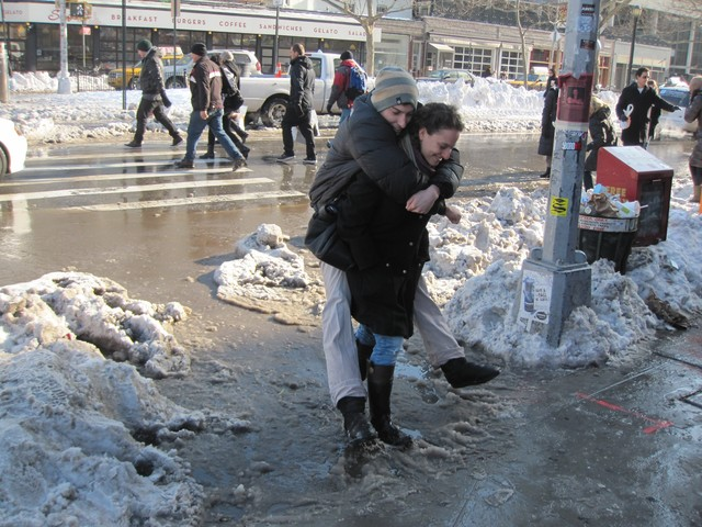 A woman gives a man a lift through a massive slush puddle at the corner of Houston and Allen streets.