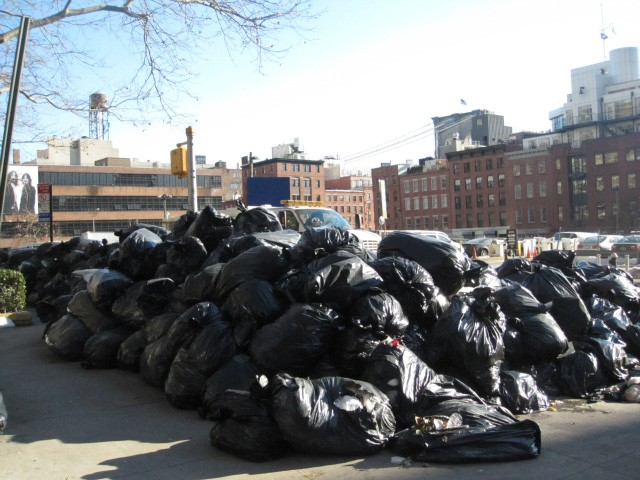 More than 100 bags of garbage sat outside the Southbridge Towers at Pearl and Beekman streets Monday morning.