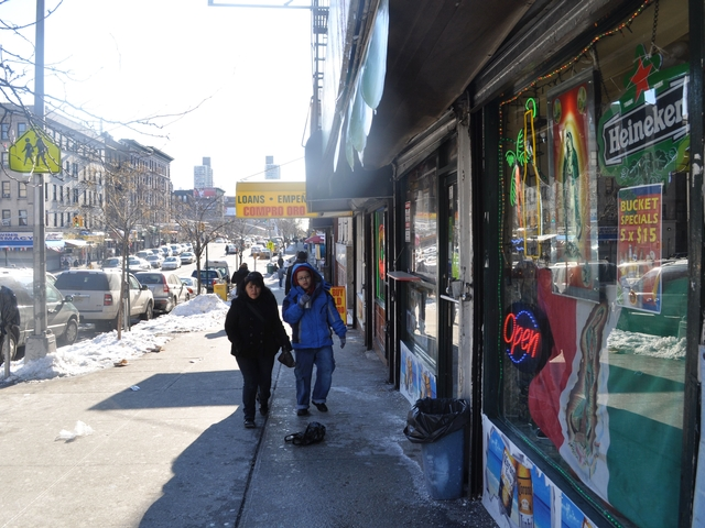 Residents walk into the bodega where a 20-year-old man was stabbed to death on the sidewalk outside on Friday.