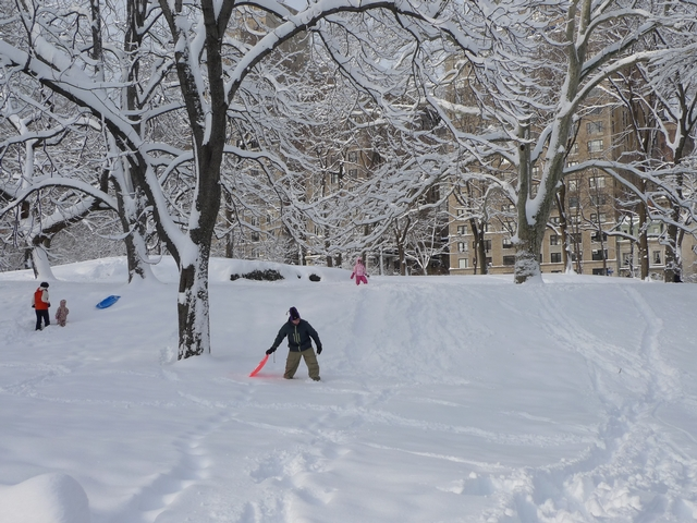 Dad Scott Goldstein clears a path for sledder Serena Goldstein, five, in Central Park.