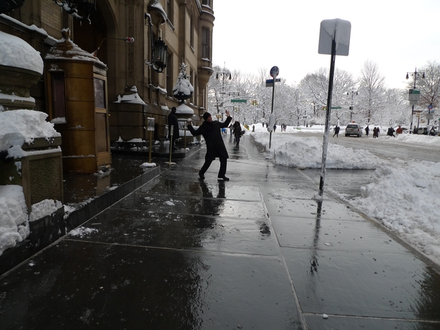 A doorman at The Dakota warms up his pitching arm with a snowball.