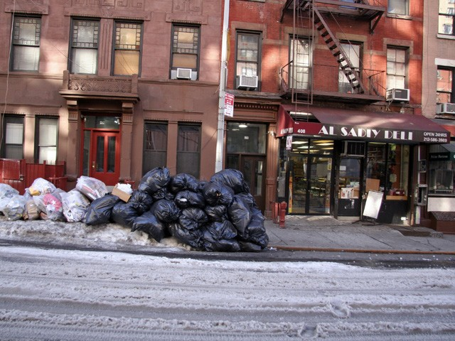 Garbage sat in front of residences and business on West 56 Street Monday morning. The next pickup for the street was scheduled for Tuesday, according to the Department of Sanitation's website.