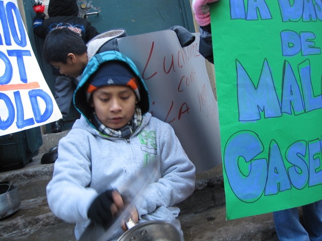 A young resident of 21 E. 115th St. bangs a pot in a protest outside of his building.