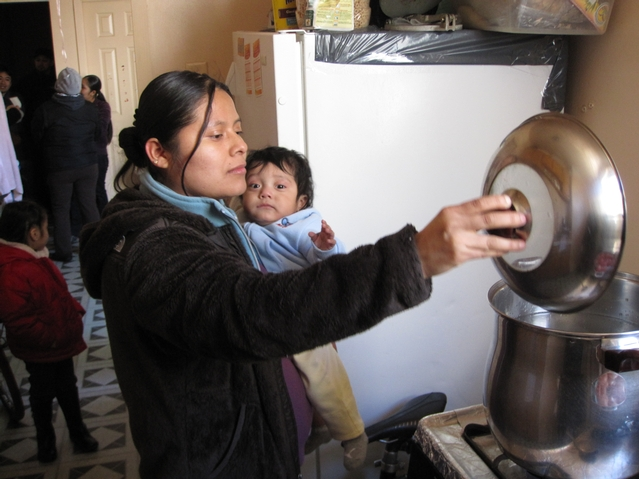 Isabel Cano, 21, checks the pots of boiling water in her kitchen. She says the lack of heat and hot water has made her 9-month-old son Jonathan sick.