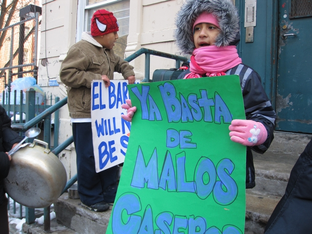 A young resident of 21 E. 115th St. protests outside of her building.