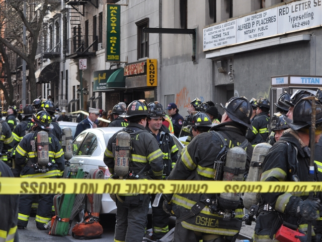 Firefighters gather at the scene of Friday's fire.